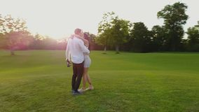 Couple Embracing And Kissing Outdoors, Shooting From Drone Circling Above, Romanic Man And Woman Walking In Park. Aerial View stock footage