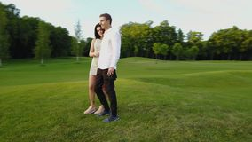 Couple Embracing And Kissing Outdoors, Shooting From Drone Circling Above, Romanic Man And Woman Walking In Park. Aerial View stock video