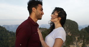 Couple embracing on mountain top, man and woman looking at each other stock video footage