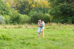 Couple embracing on nature. Young romantic man and woman standing and hugging each other with tenderness outdoors. Young Royalty Free Stock Image