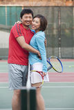 Couple embracing next to the tennis net Stock Photos