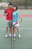 Couple embracing next to the tennis net Royalty Free Stock Image