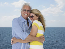 Couple Embracing With Ocean In Background Stock Image