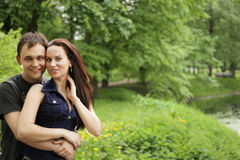 Couple embracing outdoor in park looking happy Royalty Free Stock Photo