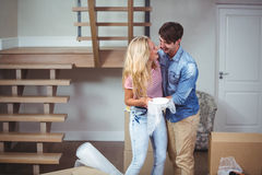Couple embracing while relocating in new house Royalty Free Stock Photos