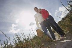 Couple Embracing On Sand Dune Stock Photo
