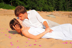 Couple embracing sitting on the sand of the beach Stock Images