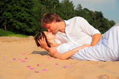 Couple embracing sitting on the sand of the beach Royalty Free Stock Images