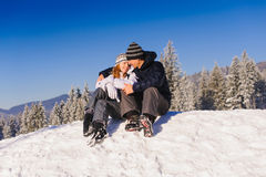 Couple embracing on ski slope. Happy couple embracing tenderly in snow at ski slope in winter mountains Royalty Free Stock Images