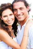 Couple embracing and smiling. Happy young couple smiling at camera and embracing each other Royalty Free Stock Image