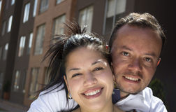 Couple embracing and smiling in front of their new first home. Stock Photo