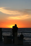 Couple embracing at sunset. Romantic couple at pier at sun set royalty free stock image