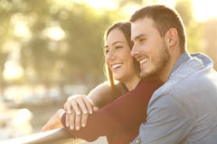 Couple embracing at sunset in a balcony. Enamored couple embracing and looking away enjoying views at sunset in a balcony with a warm light in the background Royalty Free Stock Photos