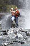 Couple Embracing Under Spray Of Waterfall Royalty Free Stock Photos
