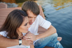 Couple embracing on a wooden pier near the river Stock Image