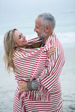Couple embracing while wrapped in a beach towel Royalty Free Stock Photography