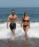 Couple  emerging from a swim  Royalty Free Stock Photo