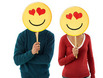 Couple with emoticon. Young adult woman and man holding emoticon with red hearts on white background. Horizontal shape, front view, waist up Stock Image