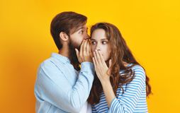 Couple of emotional people man and woman on yellow background. Couple of young emotional people men and women on yellow background royalty free stock images