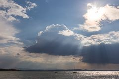 A couple of empty, little sailboat on a lake, beneath a moody sky with sun rays filtering through stock photography