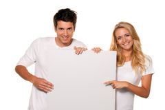 Couple with empty poster to advertise the opening Stock Photo