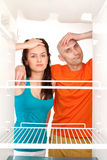 Couple with empty refrigerator. Man and woman looking into an empty refrigerator stock photos