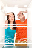 Couple with empty refrigerator Stock Images