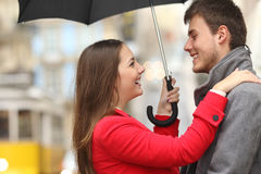 Couple encounter in the street under the rain Stock Images