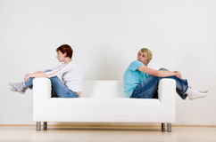 Couple on ends of couch. Man and woman couple sitting on opposite ends of a white couch Royalty Free Stock Photography