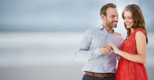 Free Couple Engaged Against Blurry Beach Stock Photos - 89405933