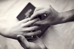 Couple engagement or marriage. A man and woman`s hand with the man placing a ring on the finger of the woman. Vintage look with black and white, grain and soft Royalty Free Stock Images