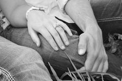 Couple with engagement ring. Black and white closeup of hands of young couple; woman wearing engagement ring Royalty Free Stock Image