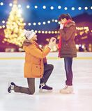 Couple with engagement ring at xmas skating rink. Love, holidays and relationships concept - happy couple with engagement ring at outdoor skating rink over stock photo