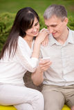 Couple engrossed with phone. Young attractive happy smiling lovers couple in love sitting on park bench on date, hugging, holding cellphone, looking at screen Royalty Free Stock Images