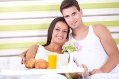 Couple enjoy in  breakfast in bed. Smiling young couple together getting ready to enjoy breakfast in bed Royalty Free Stock Image