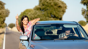 Couple enjoy freedom on car travel. Cheerful women on car travel doing thumbs up gesture. Happy brunette girl enjoying freedom on roadtrip vacation Stock Image