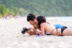 Couple enjoy and happy fun on beach laughing together looking at summer vacation travel photo pictures on retro vintage camera. Ho Stock Photography