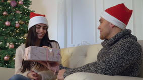 Couple enjoy new year`s eve. Pair in love or friends sitting on the sofa near christmas tree. Happy smiling man giving gift attractive caucasian brunette woman stock footage