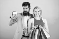Couple enjoy shopping. Man bearded hipster hold credit card and girl enjoy shopping. Ask man to purchase lots presents stock photography