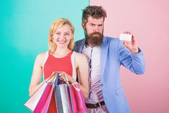 Couple enjoy shopping. Man bearded hipster hold credit card and girl enjoy shopping. Ask man to purchase lots presents royalty free stock photo
