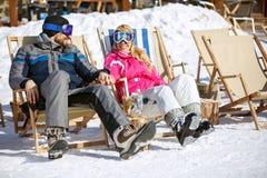 Couple enjoy at sun on ski terrain. Couple in love relax and enjoy at sun on ski terrain in mountain Stock Photo