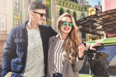 Stylish couple in sunglasses stay at street near the car stock photography