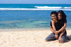 Couple enjoy vacation. Young asian couple enjoy vacation on the beach. The men holding the women Stock Photos