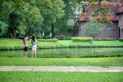 A Couple Enjoyed Feeding Fish in the Park Stock Image