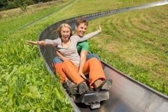 Couple Enjoying Alpine Coaster Luge. Excited young couple enjoying alpine coaster luge during summer Royalty Free Stock Image