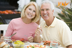 Couple Enjoying A Barbequed Meal. Sitting At Table royalty free stock photography