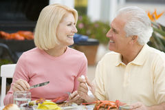 Couple Enjoying A Barbequed Meal. Sitting At Table stock image