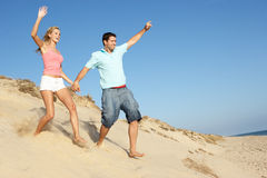 Couple Enjoying Beach Holiday Running Down Dune. In The Sun Stock Photography
