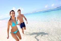 Couple enjoying beach time. Couple running on a sandy beach Stock Photos