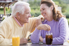 Couple Enjoying A Beverage By A Golf Course Royalty Free Stock Photography